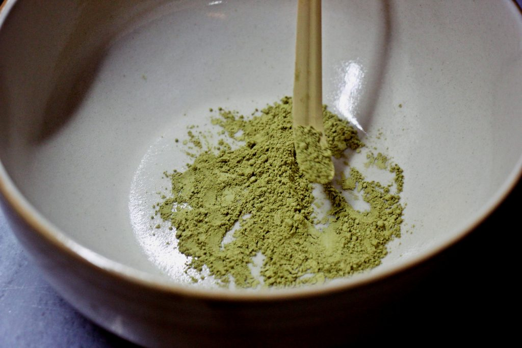 Spoonful matcha sifted in a bowl.